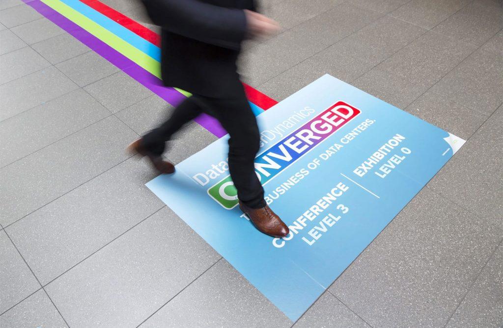 Uomo che cammina su grafica stampata su pellicola antiscivolo informazioni fiera e centri congressi